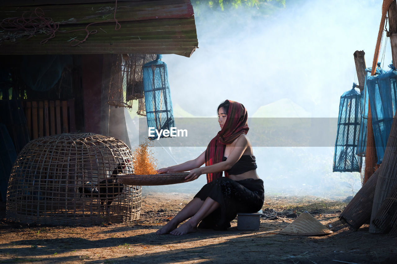 Full Length Of Young Woman Cleaning Food While Sitting On Field