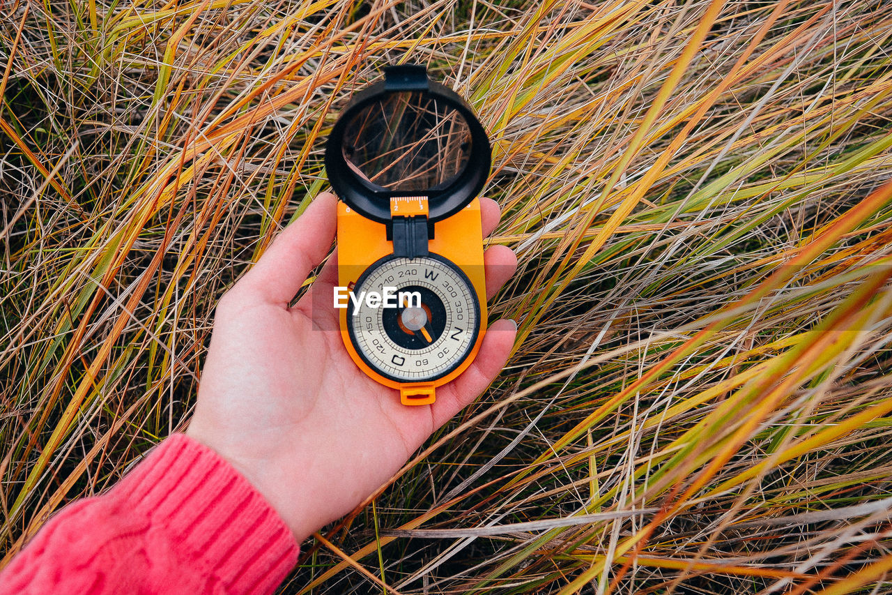 Close-up of hand holding navigational compass