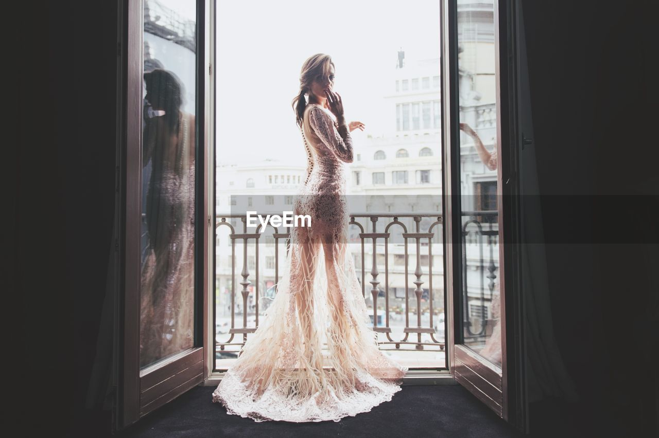 one person, real people, window, indoors, rear view, long hair, standing, day, full length, young adult, architecture, wedding dress, young women, people