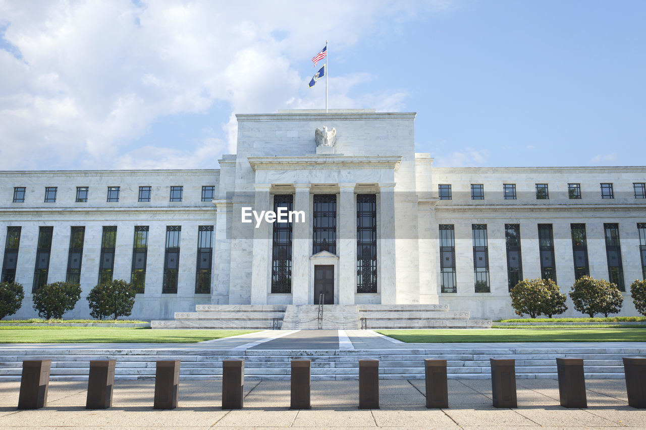 American Flag On Federal Reserve Bank Against Sky In City