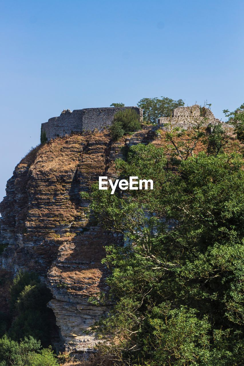 sky, plant, history, architecture, nature, built structure, clear sky, the past, ancient, day, no people, old ruin, tree, travel destinations, rock, blue, solid, travel, tourism, mountain, outdoors, ancient civilization, ruined, archaeology