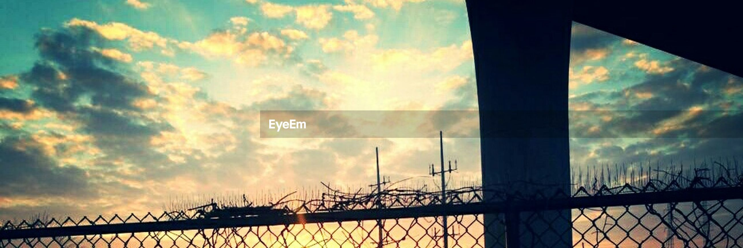 sky, cloud - sky, silhouette, cloudy, sunset, low angle view, built structure, cloud, architecture, metal, connection, railing, dusk, nature, bridge - man made structure, no people, outdoors, water, weather, engineering