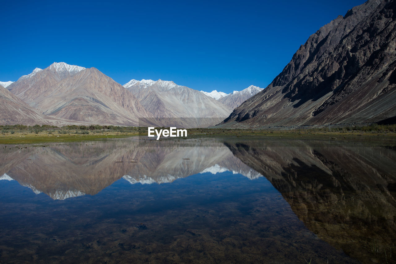 mountain, reflection, scenics - nature, tranquil scene, tranquility, sky, beauty in nature, mountain range, lake, water, blue, day, nature, idyllic, non-urban scene, landscape, waterfront, no people, environment, outdoors, snowcapped mountain