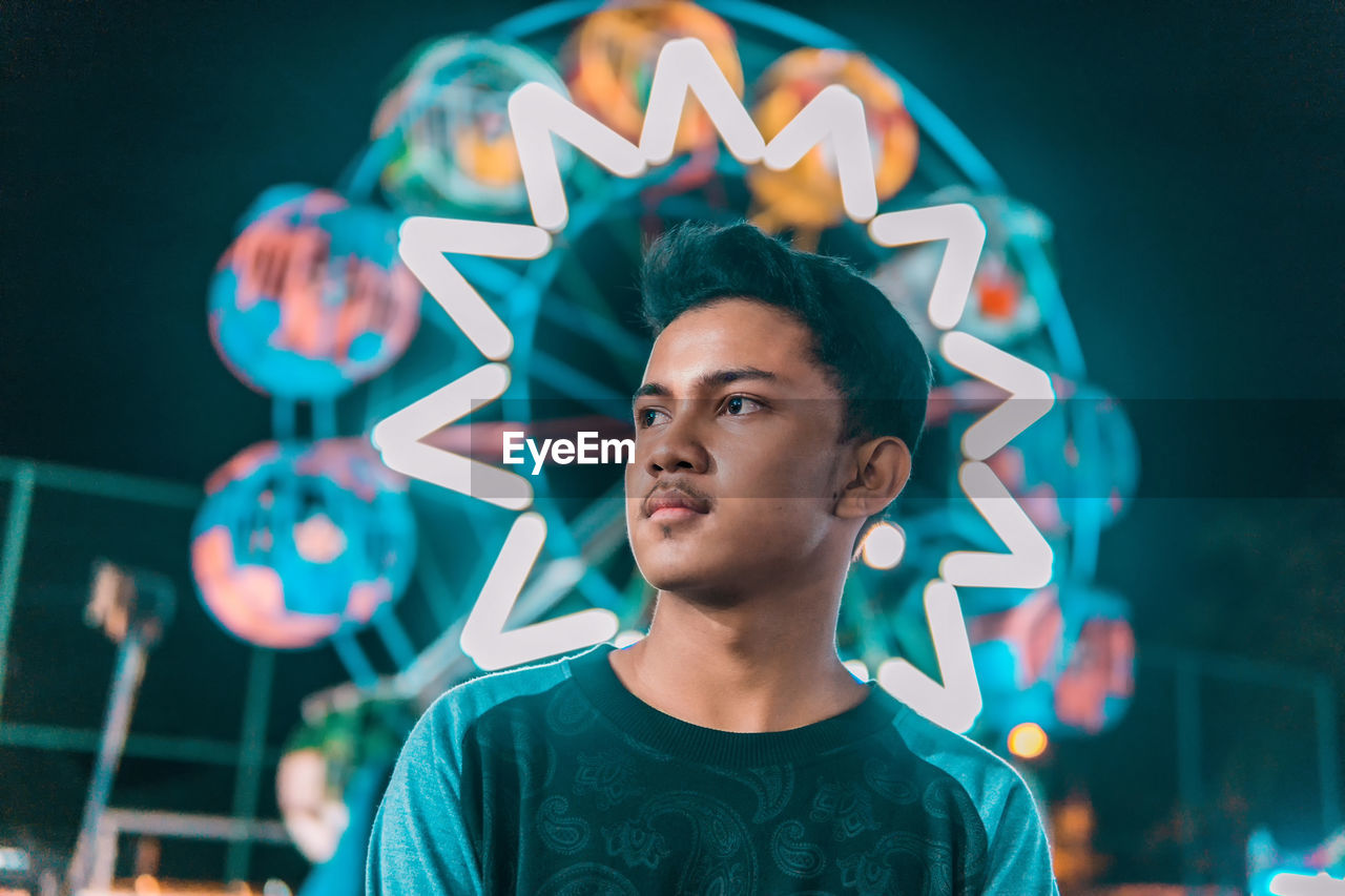 Young Man Looking Away Against Illuminated Ferris Wheel At Night