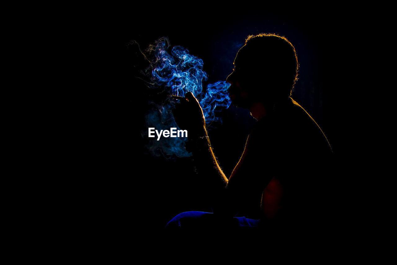 Man Smoking Cigarette Against Black Background