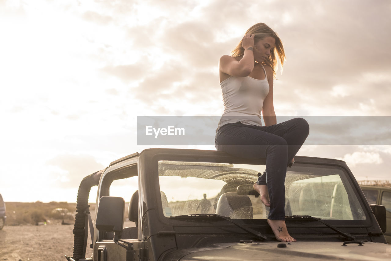 Full Length Of Young Woman Sitting On Off-Road Vehicle Against Sky During Sunset