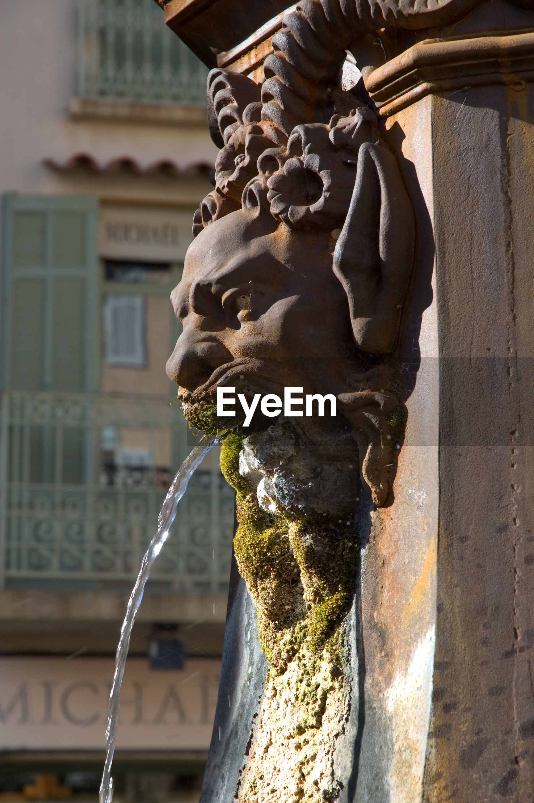 CLOSE-UP OF SCULPTURE AGAINST FOUNTAIN BUILDING