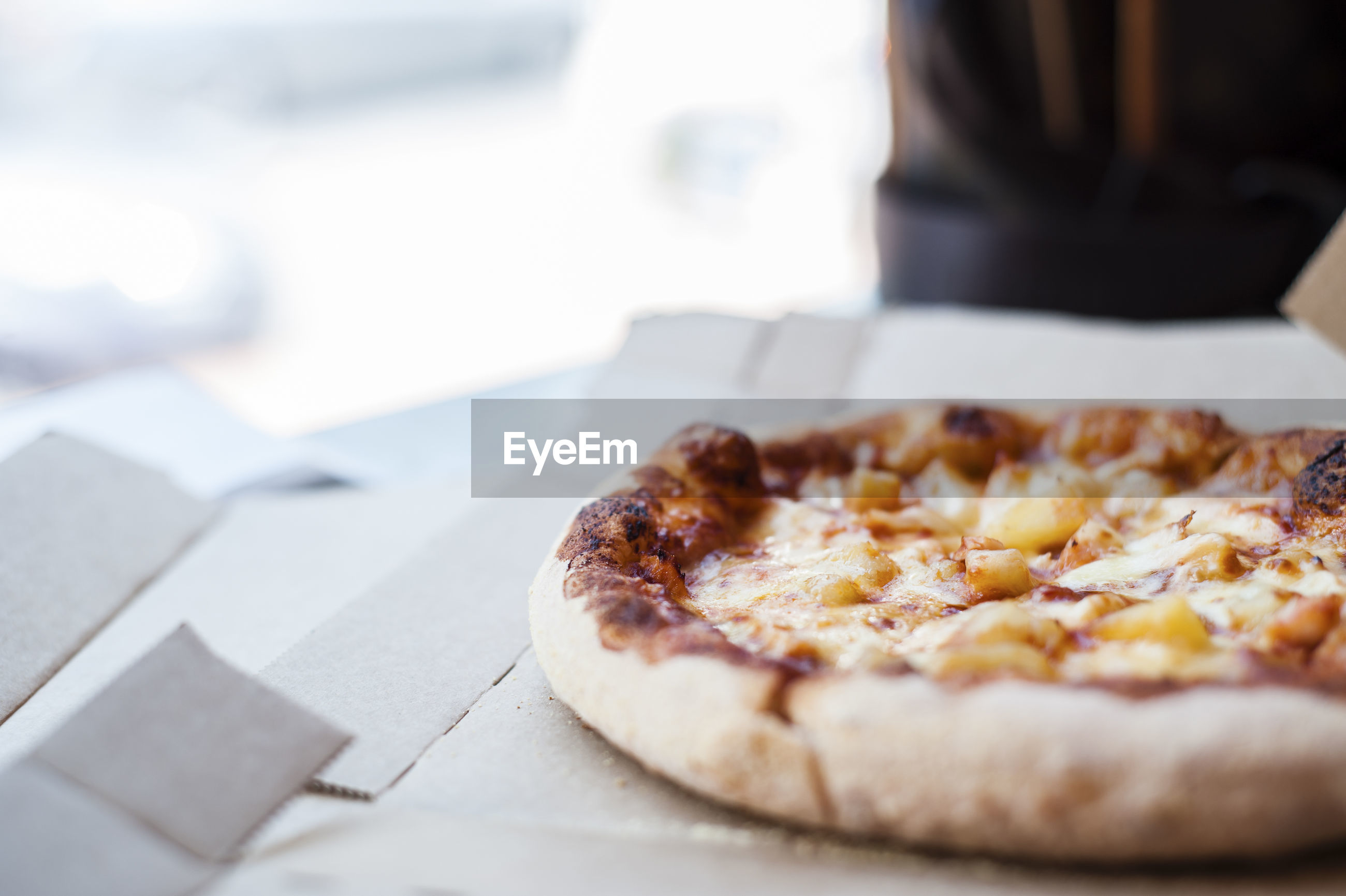 Cropped image of pizza in box against person