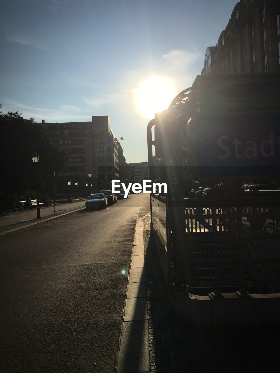 sky, transportation, sunlight, architecture, lens flare, city, sun, mode of transportation, nature, motor vehicle, car, building exterior, sunbeam, road, built structure, sunset, street, sign, land vehicle, text, no people, outdoors, bright