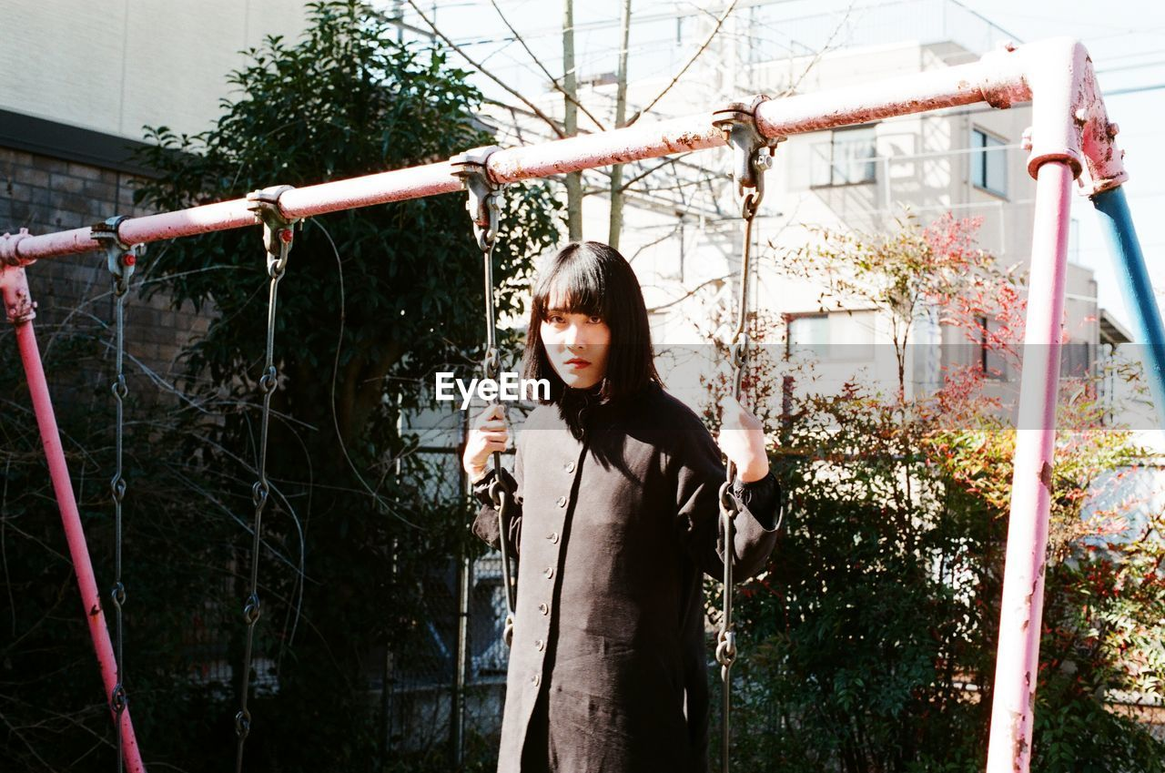 Portrait Of Serious Young Woman On Swing