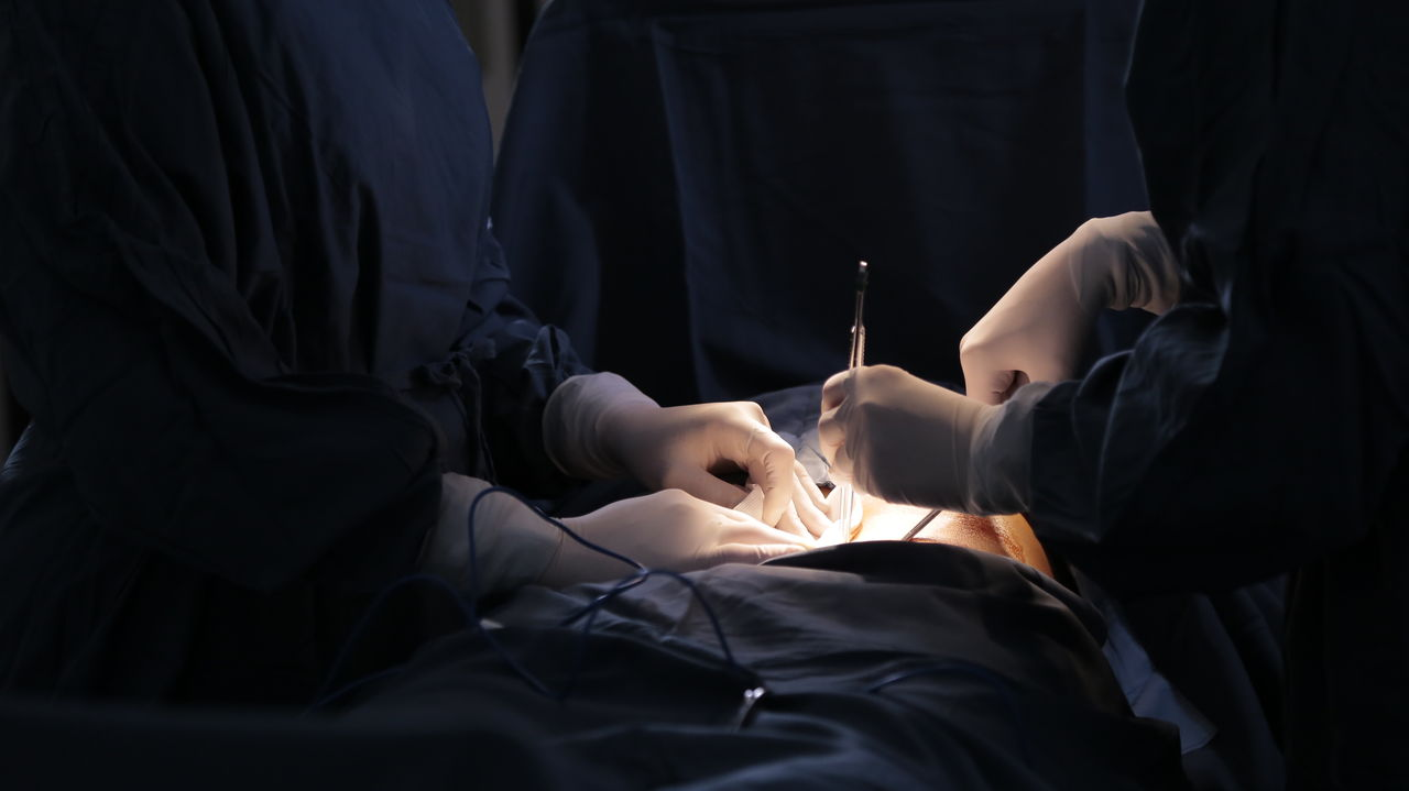 Midsection Of Surgeons Operating Patient In Hospital