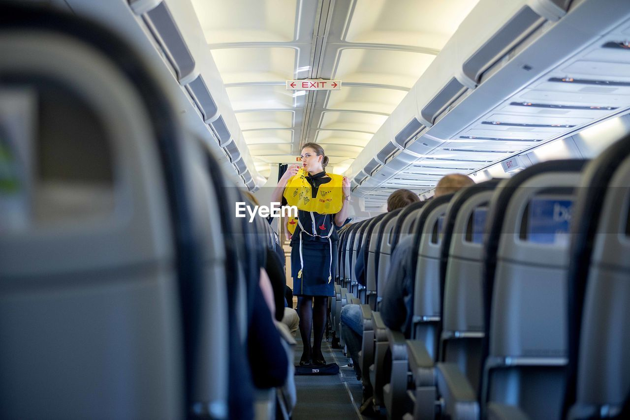transportation, mode of transportation, real people, one person, travel, vehicle interior, public transportation, portrait, men, vehicle seat, rail transportation, front view, airplane, indoors, standing, looking at camera, train, lifestyles