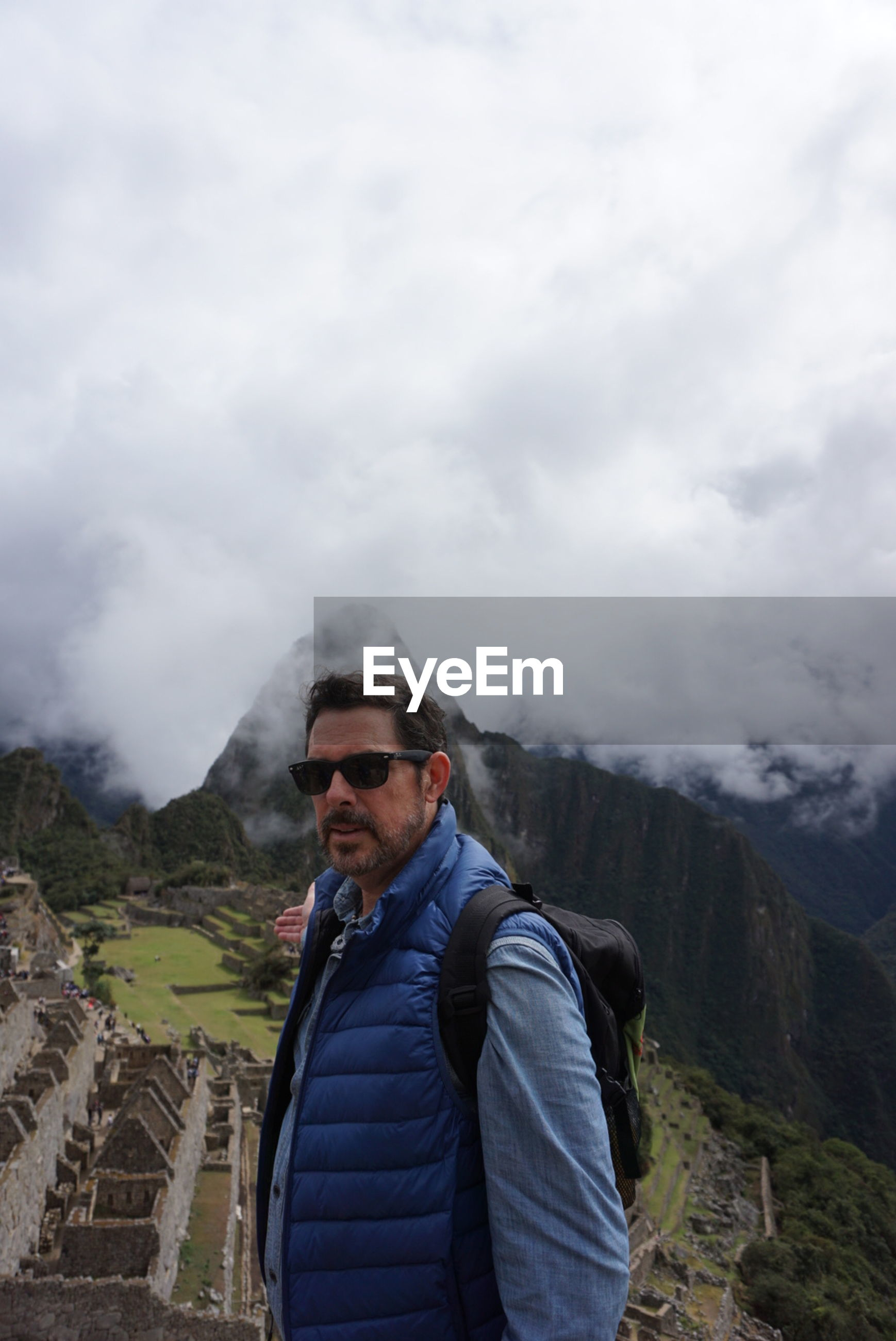 Man standing by machu picchu against cloudy sky