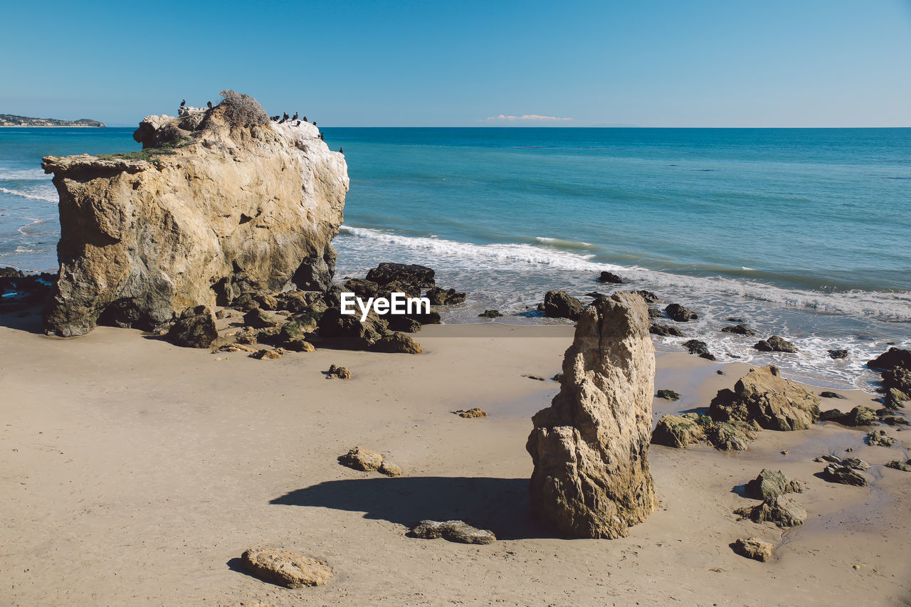 sea, horizon over water, nature, rock - object, tranquil scene, water, beauty in nature, scenics, tranquility, beach, sky, clear sky, day, sand, no people, outdoors, sunlight, blue