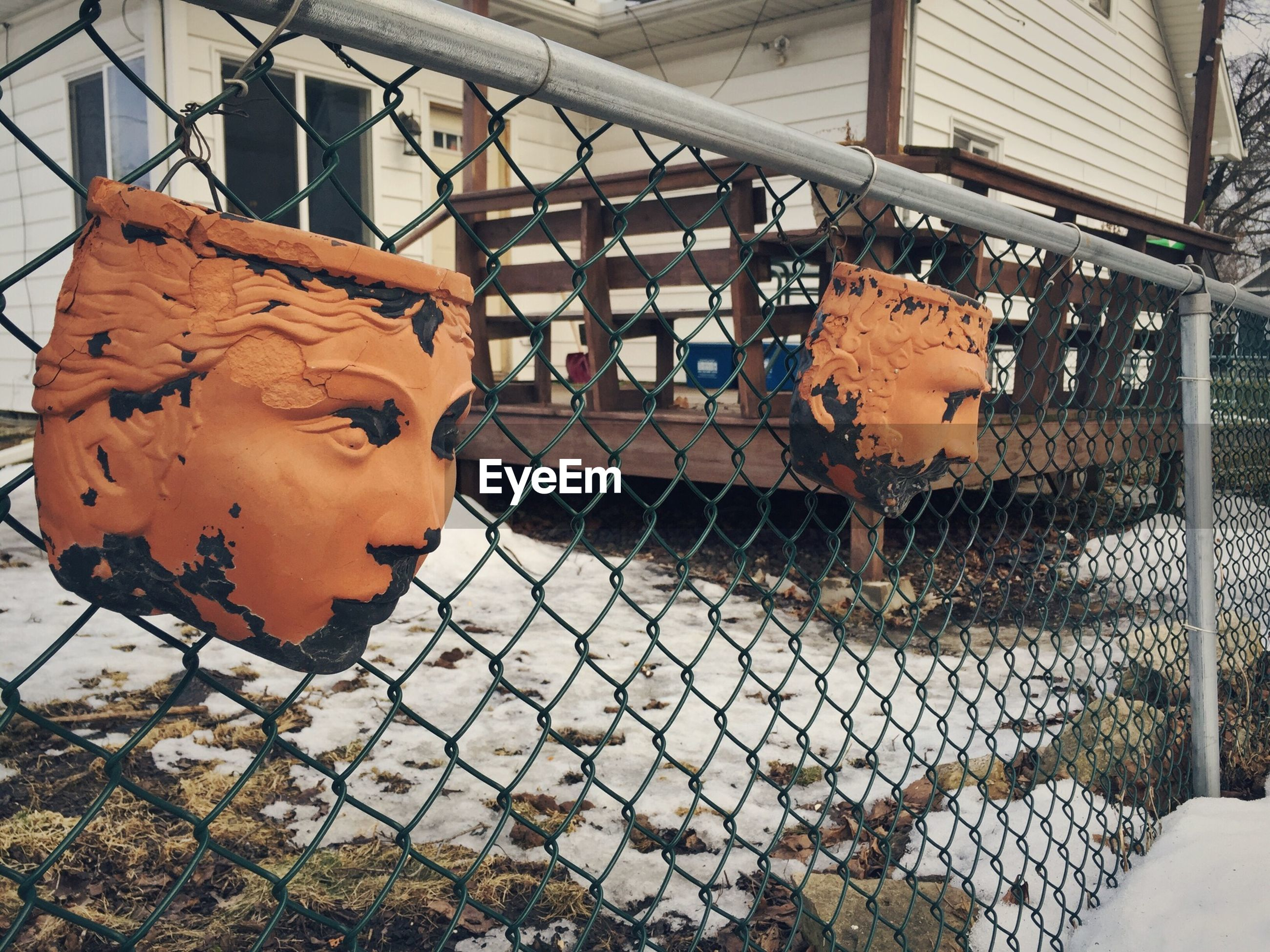 Sculptures on chainlink fence by house during winter