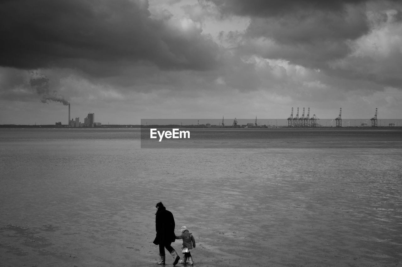 Female Walking With Girl On Damp Sand Surface, Industrial Structures On Horizon