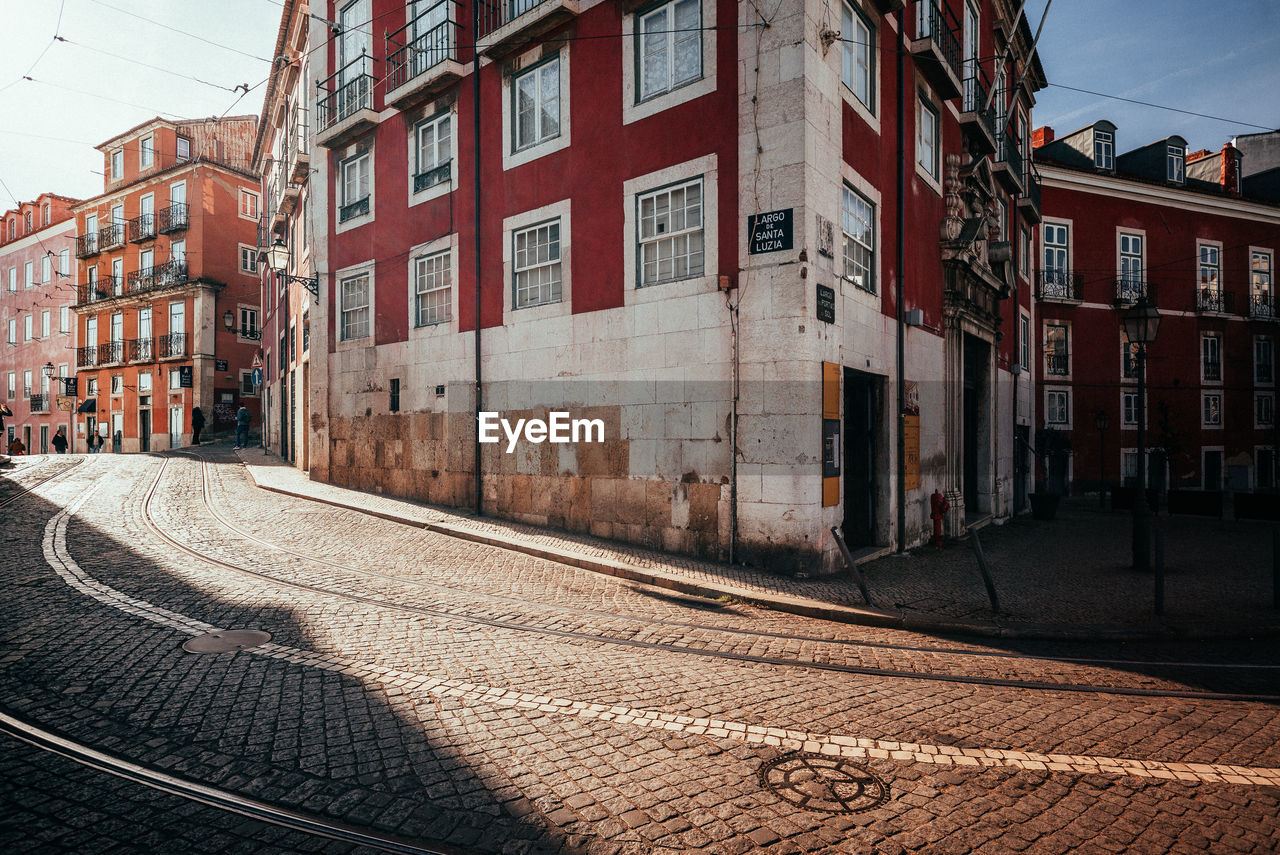 architecture, building exterior, built structure, city, building, residential district, transportation, street, window, day, no people, nature, outdoors, direction, rail transportation, sky, track, cobblestone, footpath, the way forward, row house