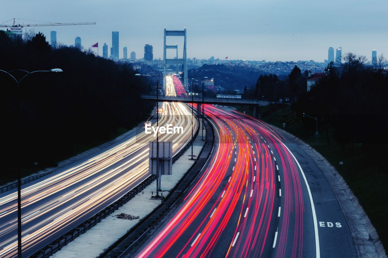 road, transportation, long exposure, light trail, motion, illuminated, city, built structure, speed, architecture, traffic, blurred motion, nature, curve, highway, red, sky, street, tree, no people, multiple lane highway, outdoors