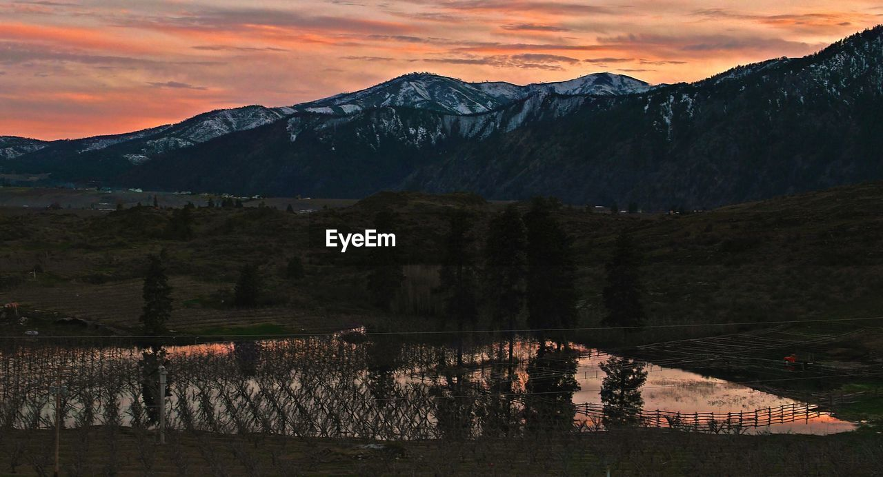 Flooded Farmland Against Mountains During Sunset