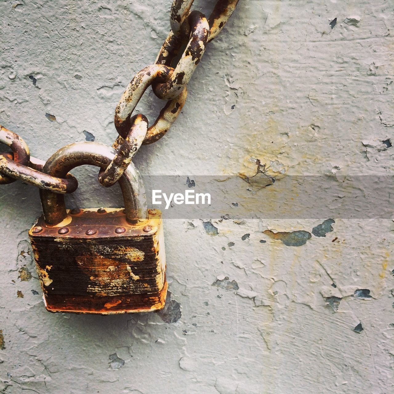 Close-Up Of Lock And Chains Against Weathered Wall