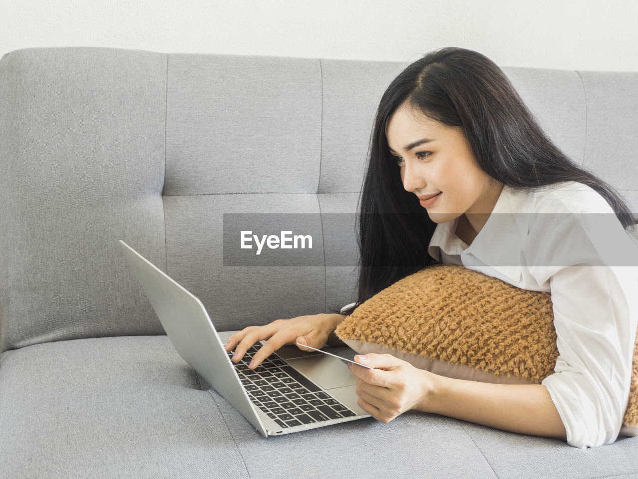 wireless technology, laptop, computer, one person, technology, using laptop, connection, real people, indoors, sitting, communication, women, young women, lifestyles, sofa, furniture, young adult, adult, internet, hair, hairstyle, beautiful woman, surfing the net