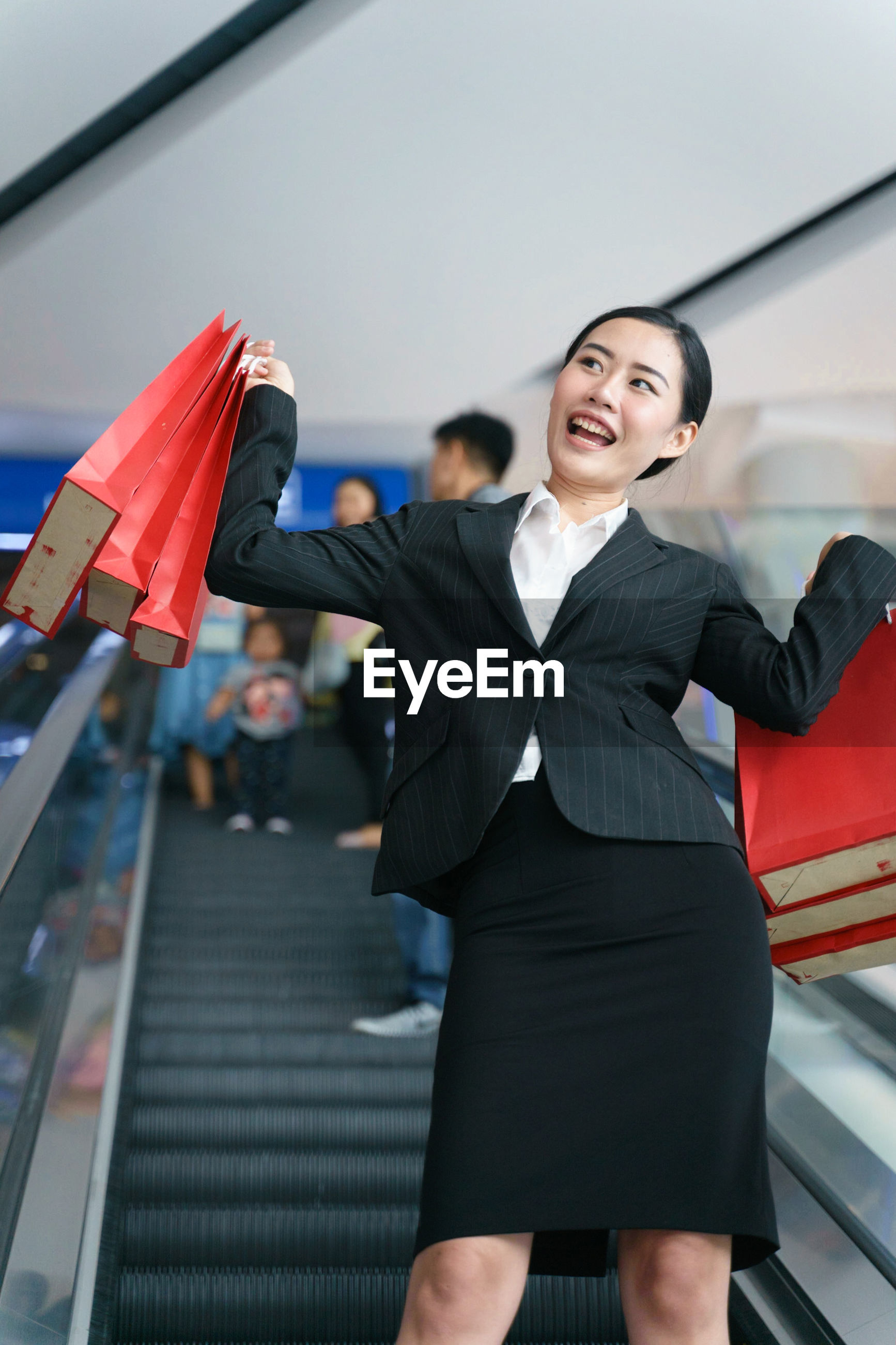 Smiling businesswoman holding shopping bags while standing on escalator at mall
