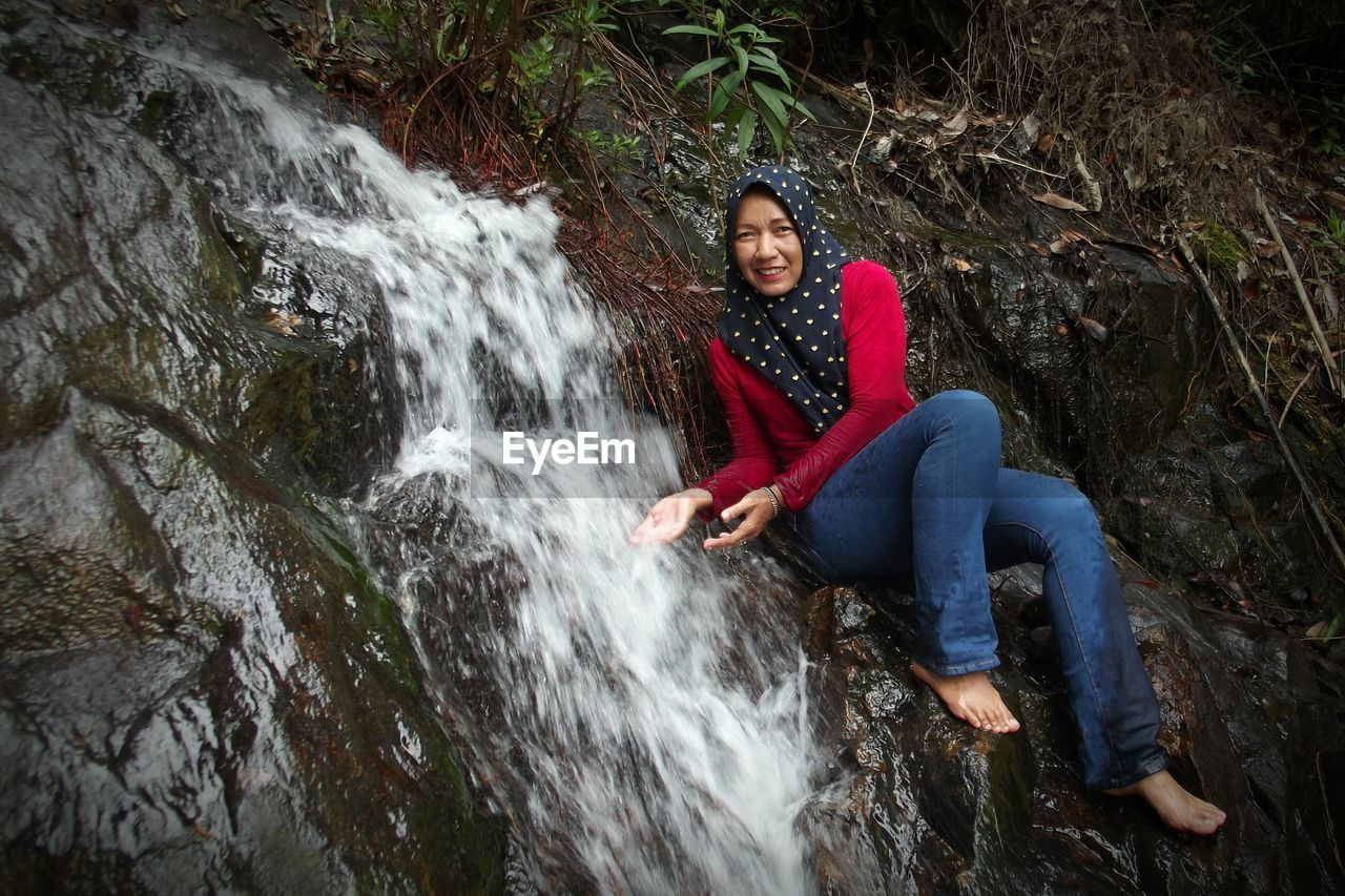 water, rock, young adult, leisure activity, one person, rock - object, full length, waterfall, motion, solid, sitting, nature, blurred motion, flowing water, casual clothing, forest, young women, smiling, outdoors, beautiful woman