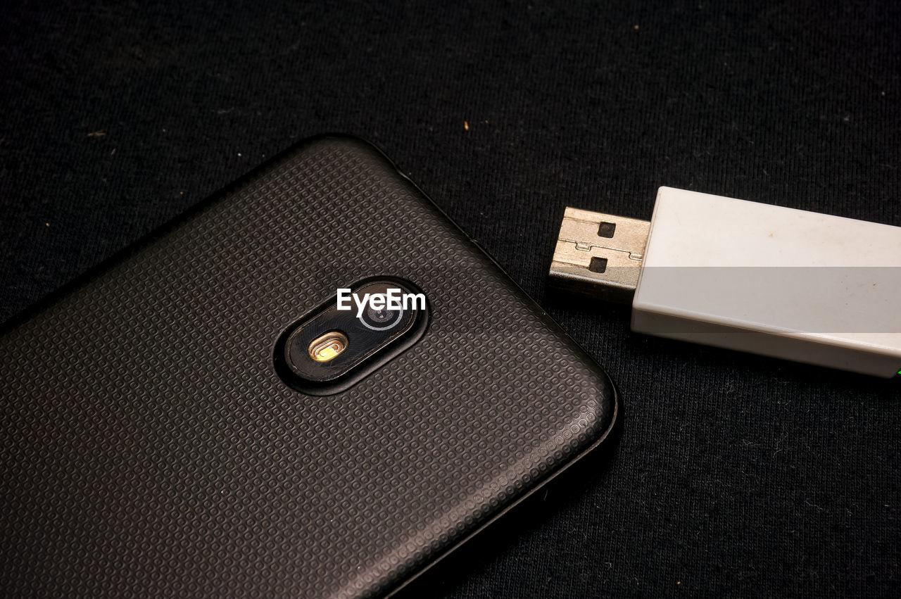 High angle view of mobile phone and usb drive on table