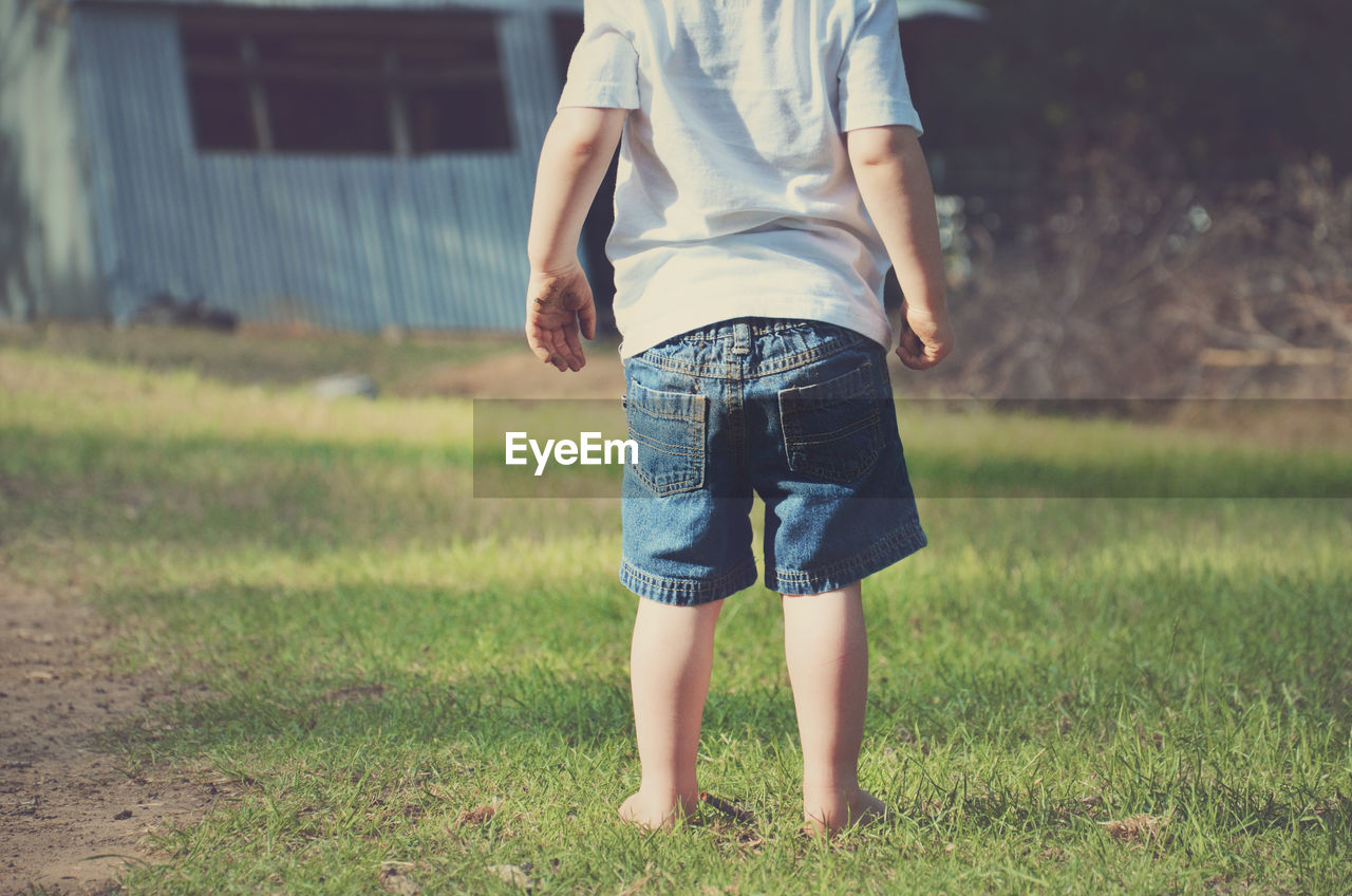 Low section of boy standing on grass in back yard