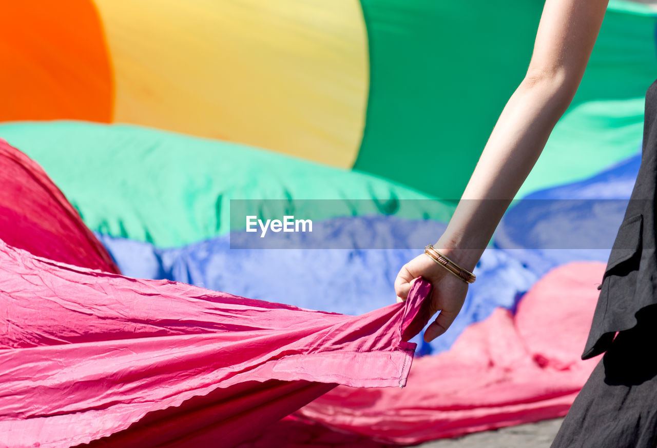 Cropped image of woman holding fabric parachute during sunny day