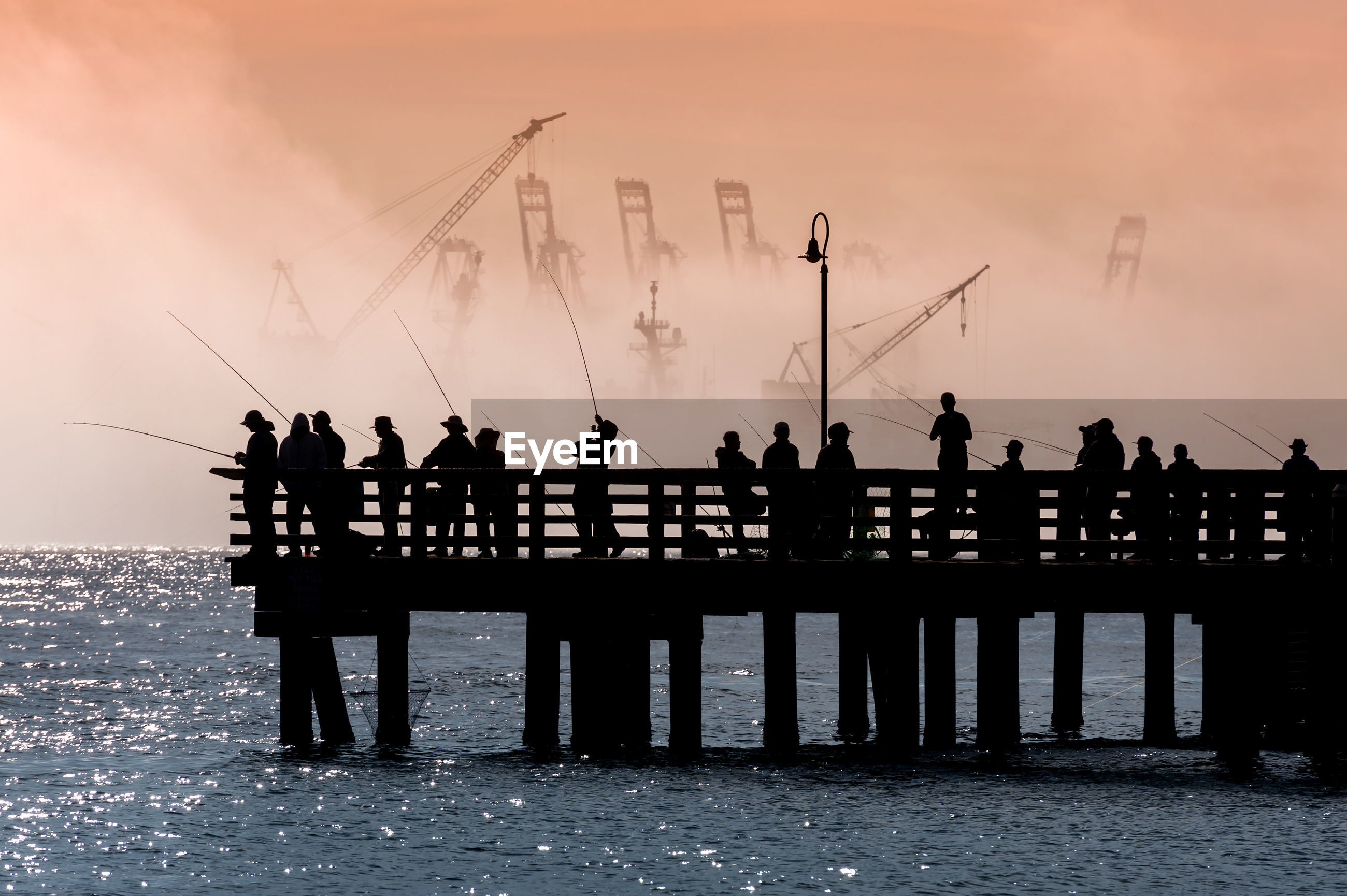 Silhouette people on pier by sea against sky during sunrise