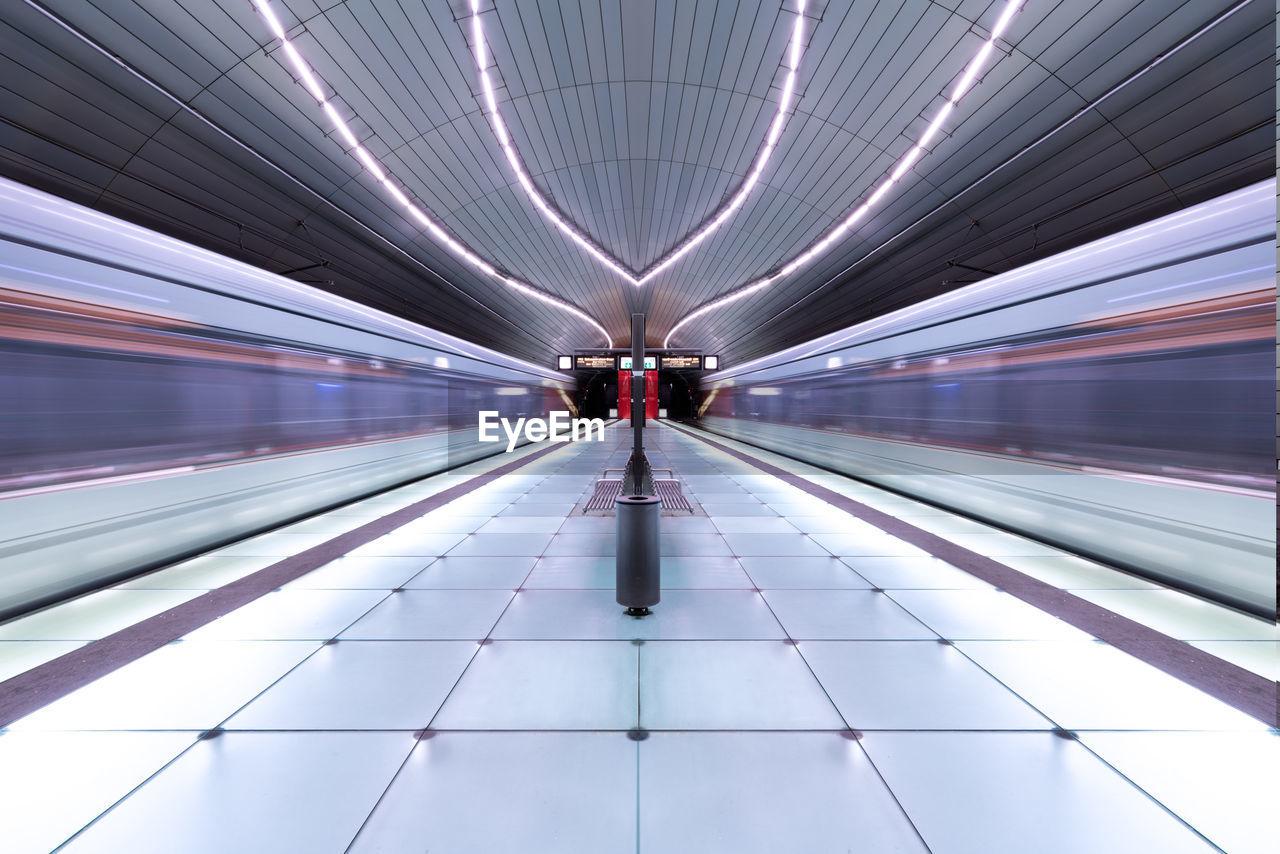 Diminishing perspective of illuminated railroad station platform