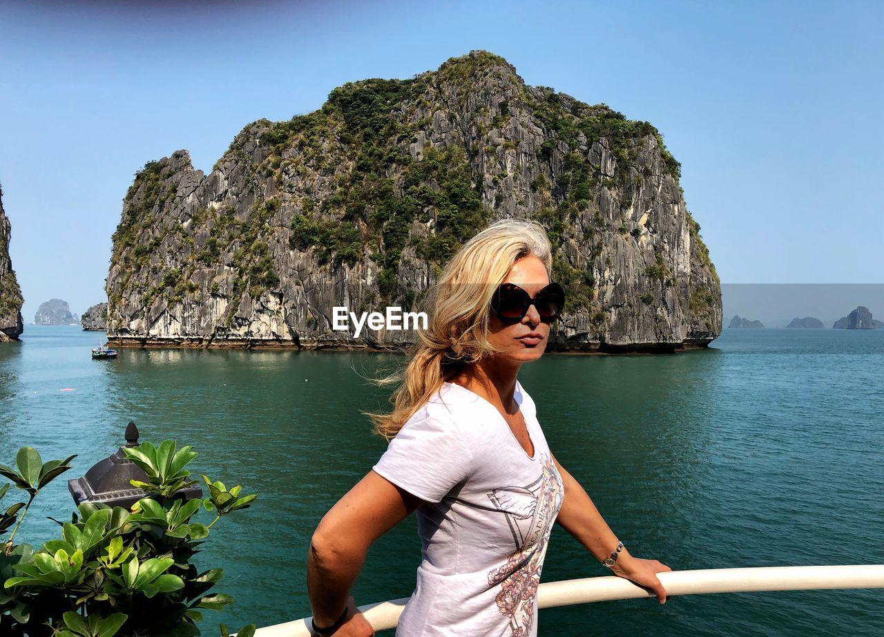 Woman wearing sunglasses against sea