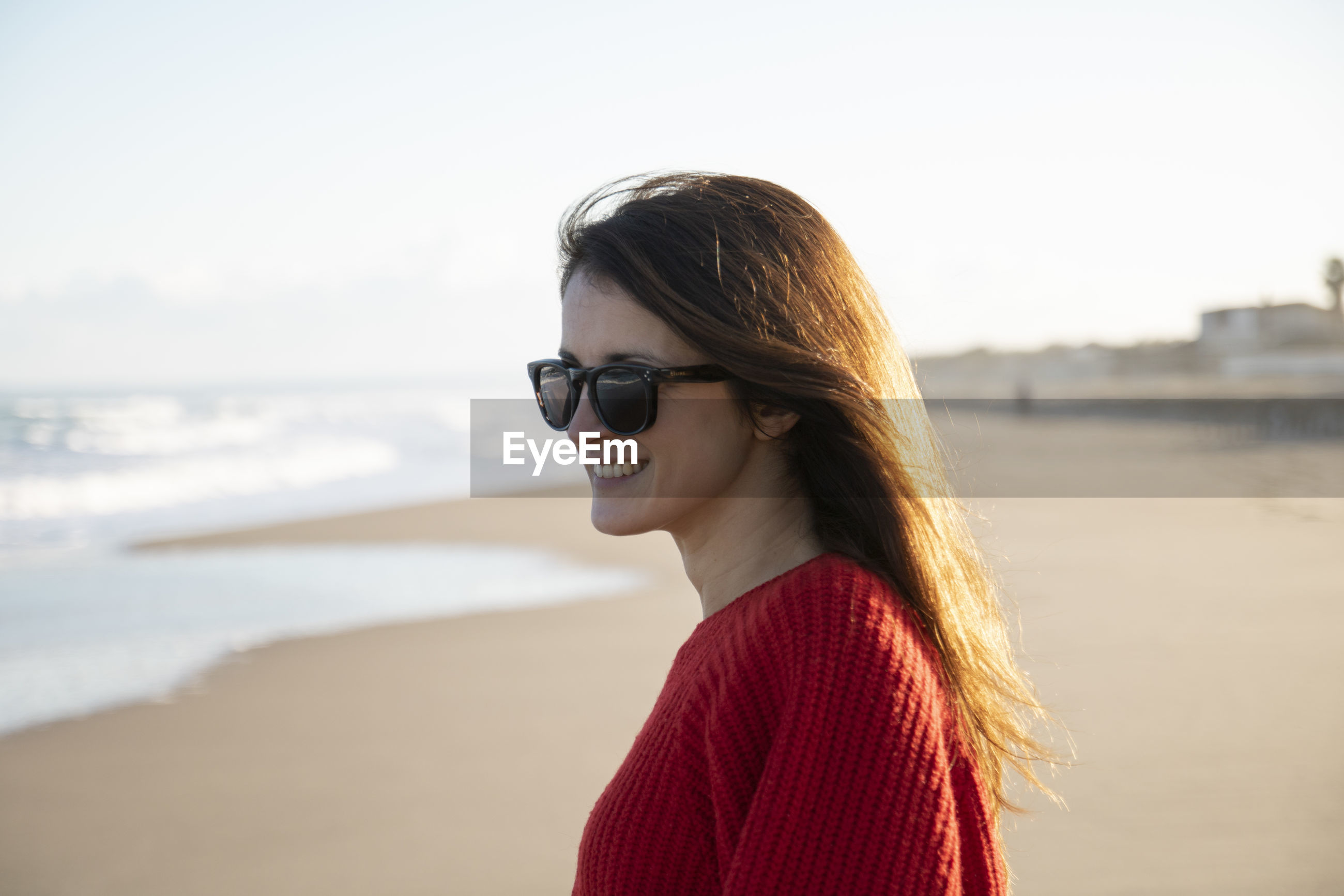 PORTRAIT OF BEAUTIFUL YOUNG WOMAN WEARING SUNGLASSES STANDING AGAINST SEA