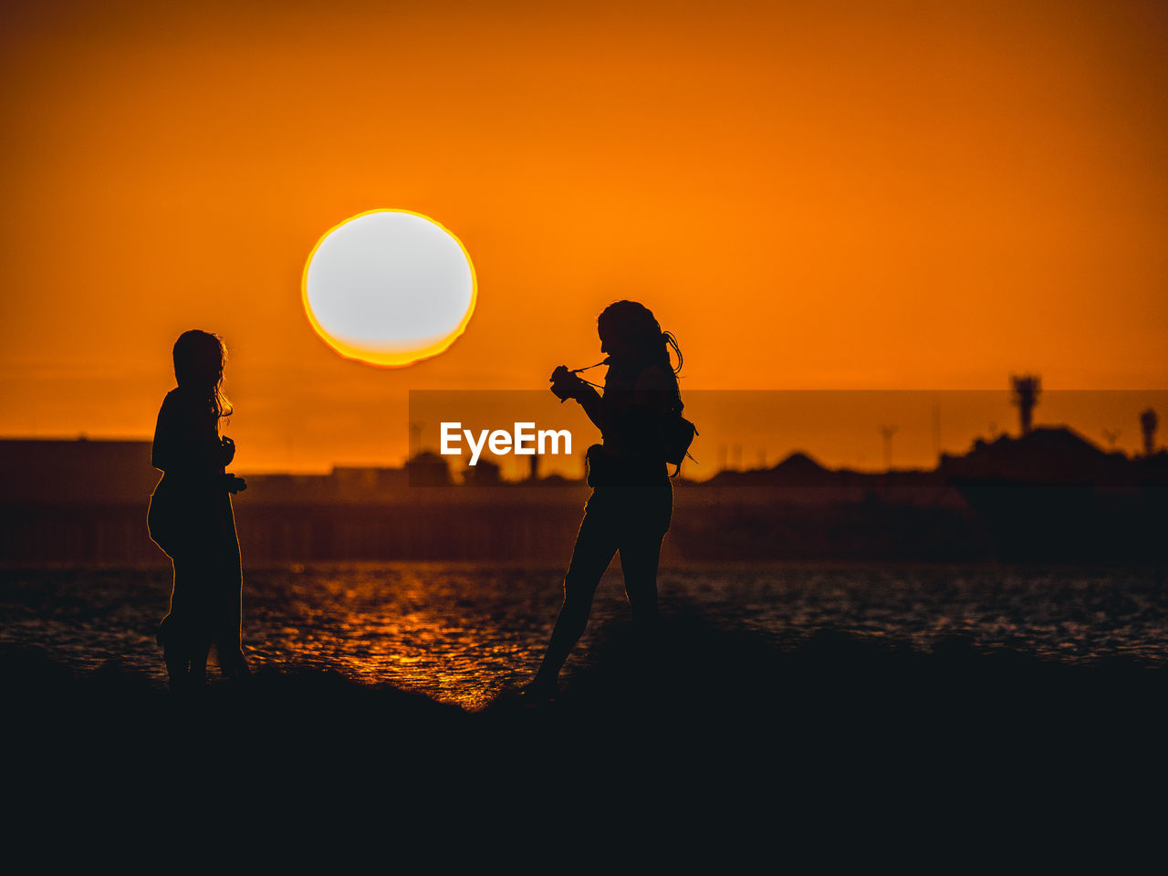 sunset, orange color, silhouette, sky, real people, two people, land, beach, lifestyles, water, sun, leisure activity, beauty in nature, standing, sea, nature, women, men, scenics - nature, togetherness, outdoors