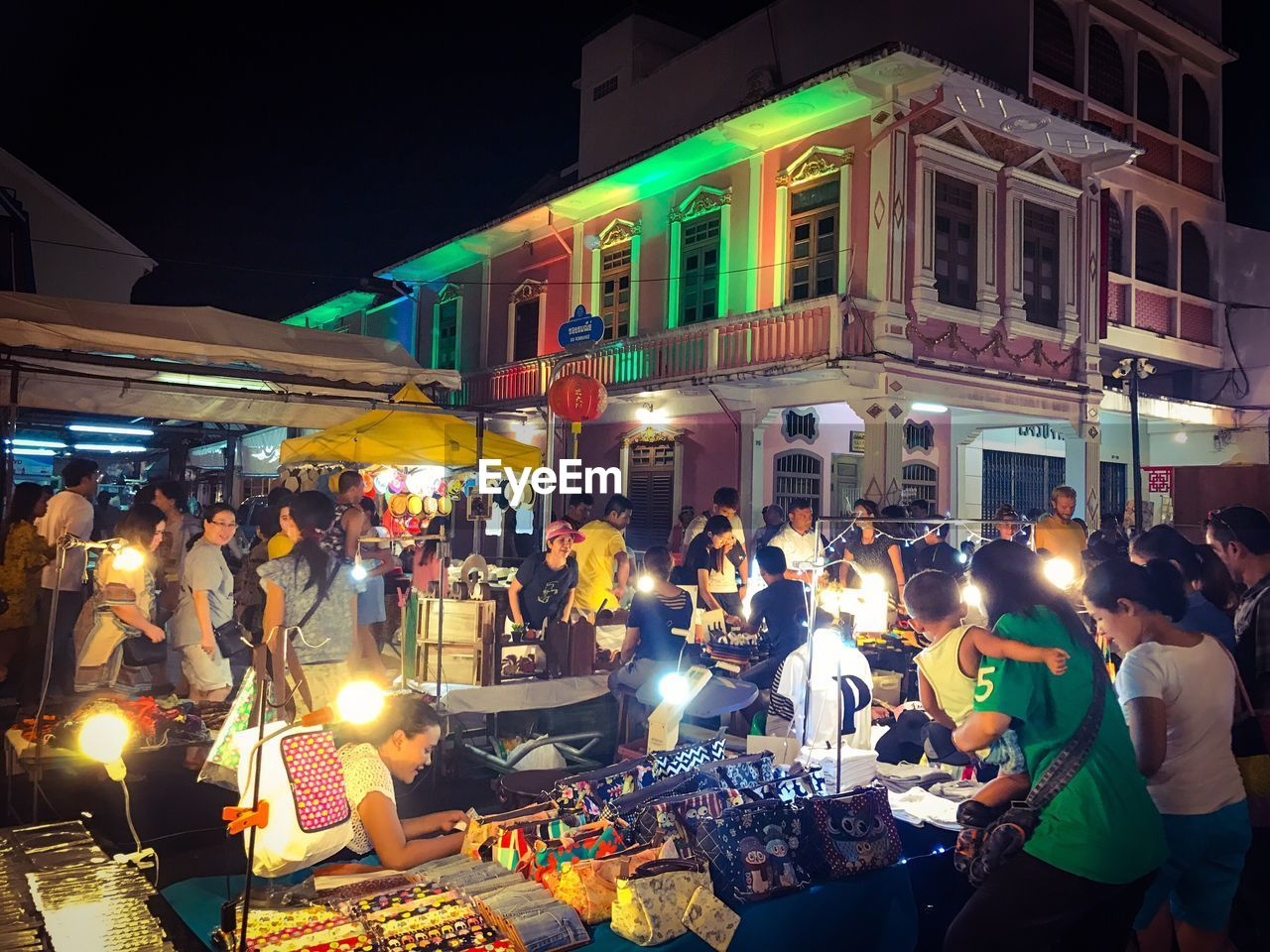 large group of people, night, illuminated, real people, men, women, crowd, building exterior, lifestyles, architecture, built structure, mixed age range, outdoors, leisure activity, market, city, food, people, adult