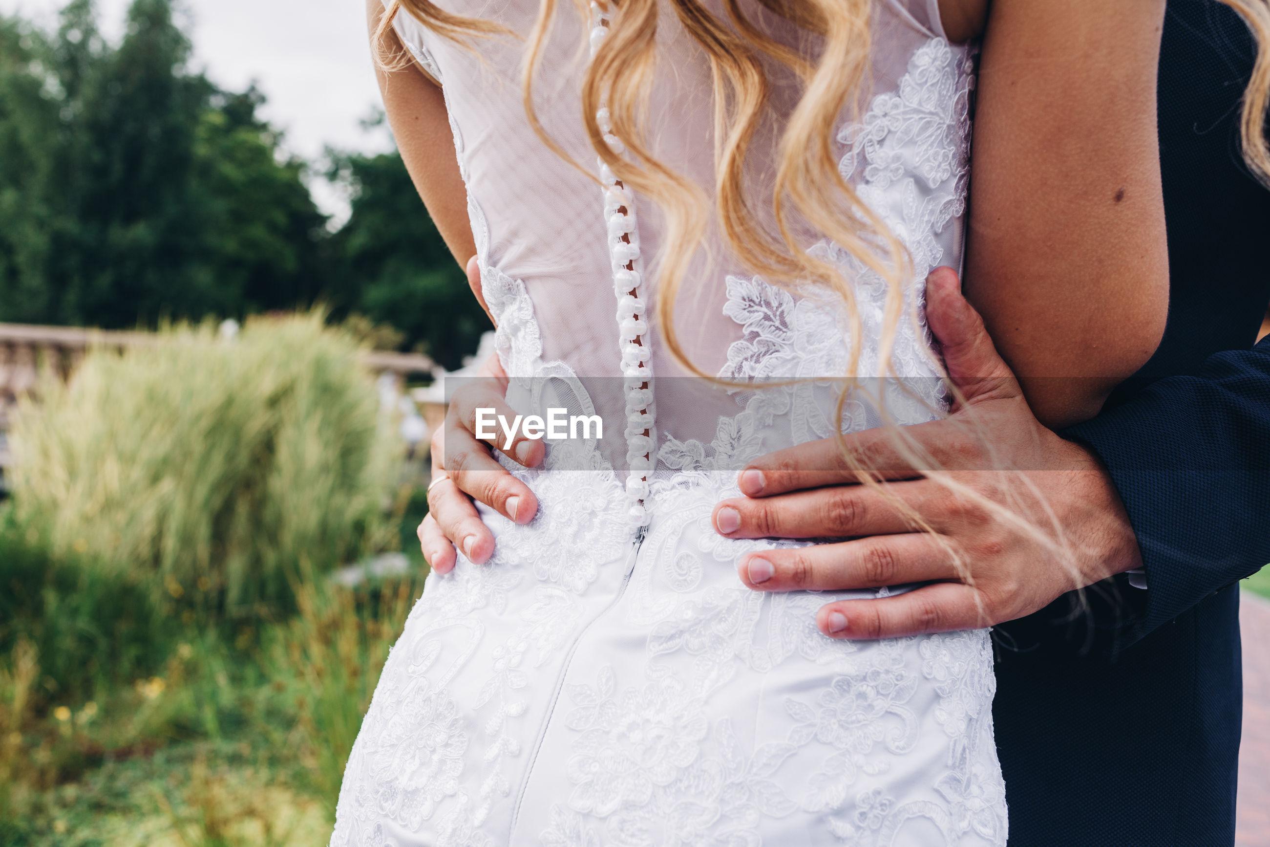 Midsection of bride embracing bridegroom during wedding ceremony