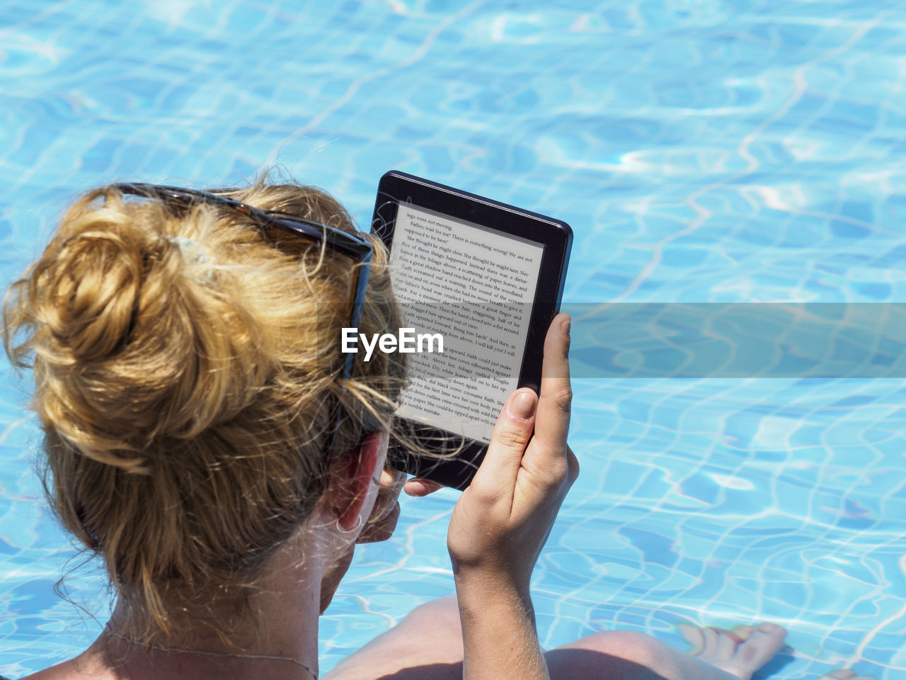 Rear View Of Woman Using Digital Tablet While Sitting At Poolside