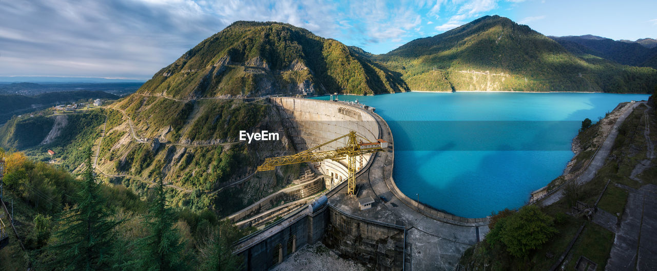 Panoramic View Of Hydroelectric Dam And Mountain Range Against Sky