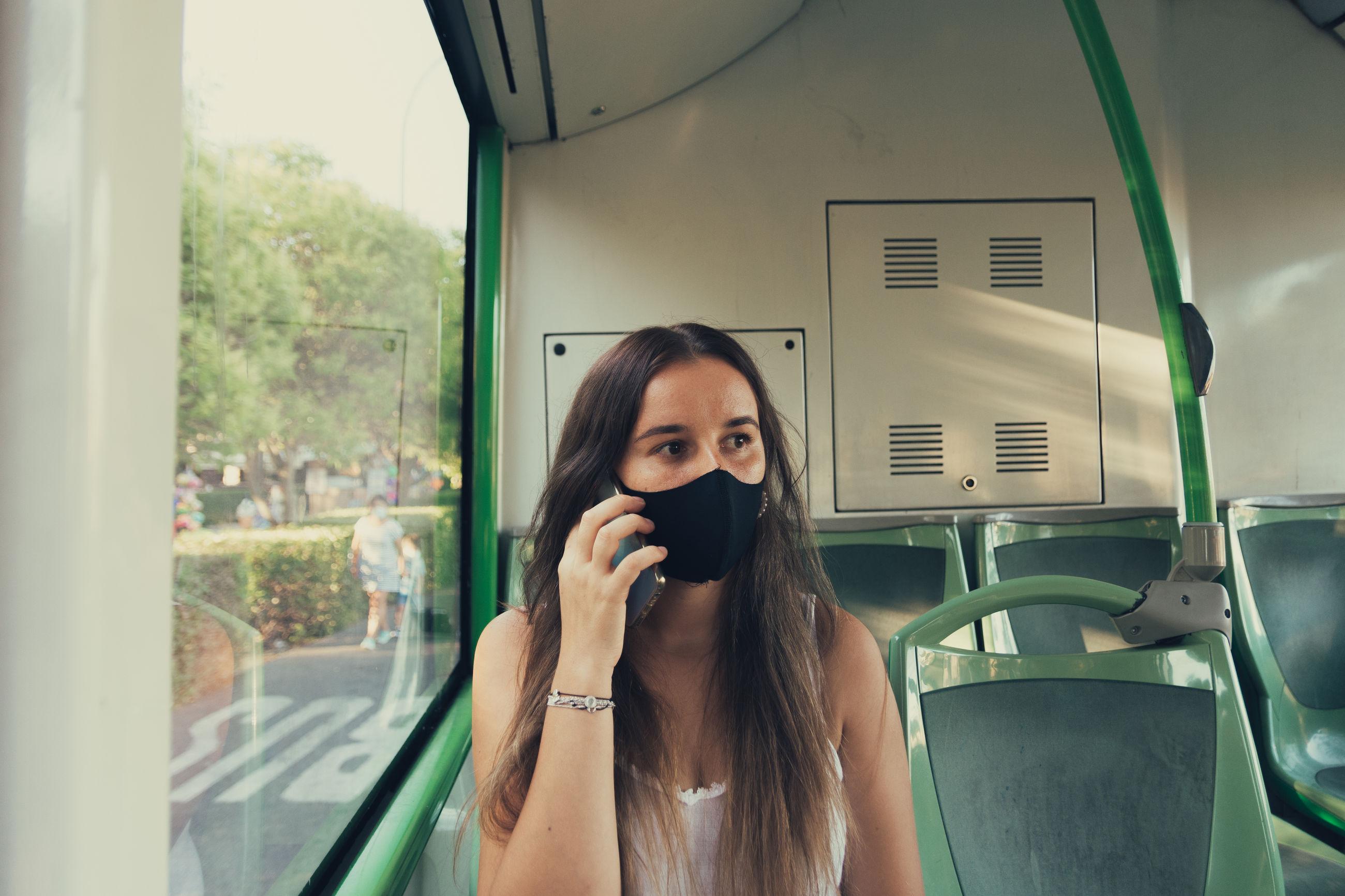 Woman wearing mask sitting in bus
