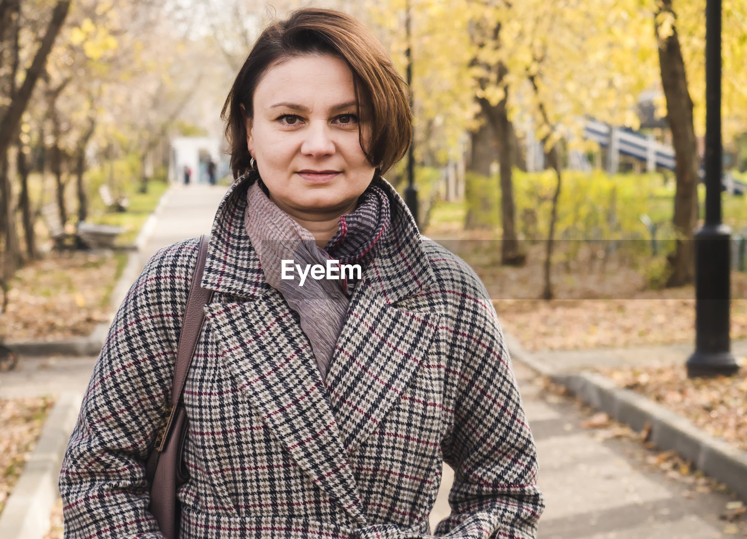 Portrait of smiling woman standing against trees on footpath in park