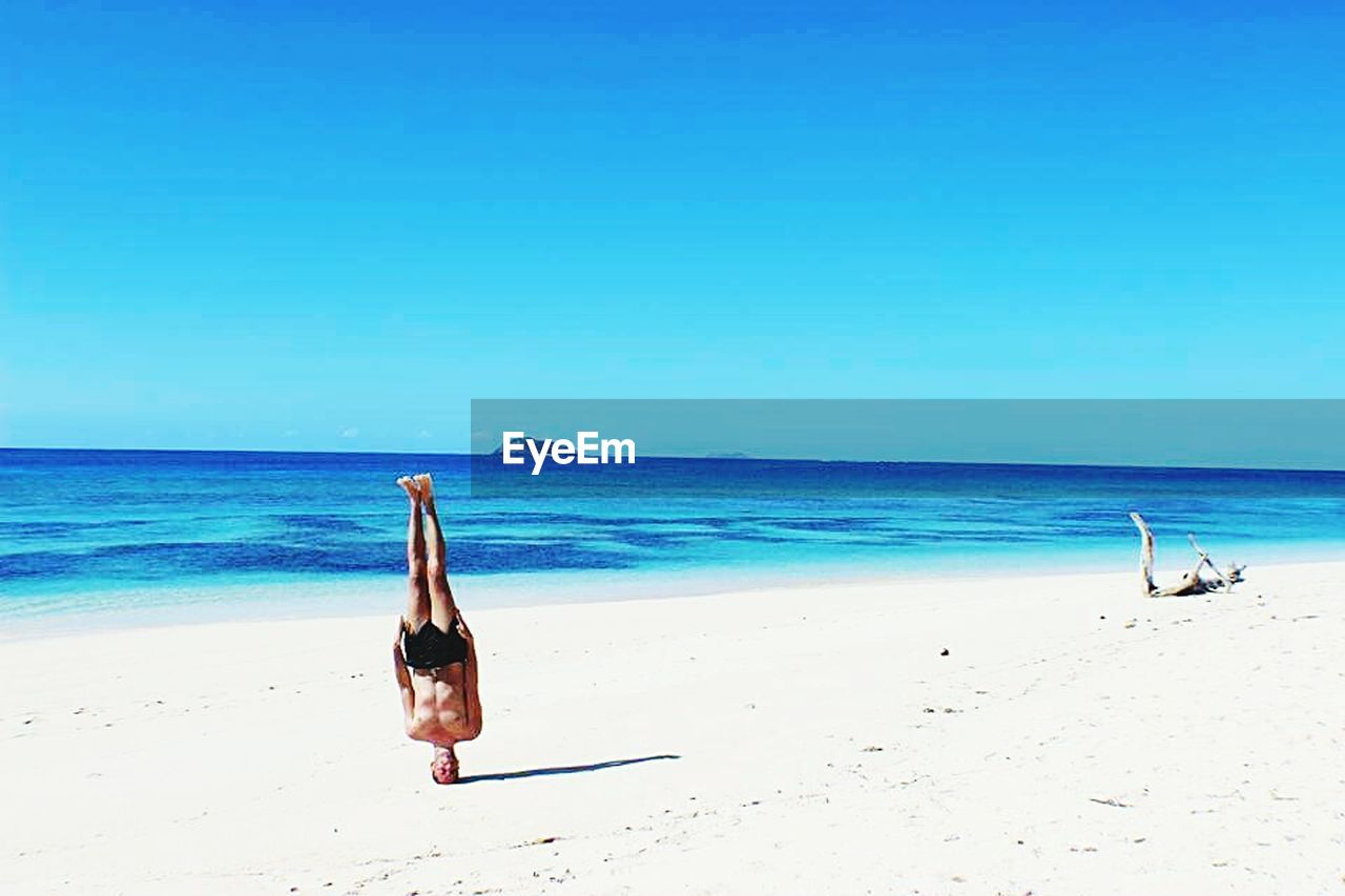 sea, beach, sand, water, shore, horizon over water, beauty in nature, nature, scenics, yoga, one person, blue, leisure activity, clear sky, tranquil scene, real people, day, outdoors, bikini, full length, summer, vacations, sky, young adult, lifestyles, young women, animal themes, people