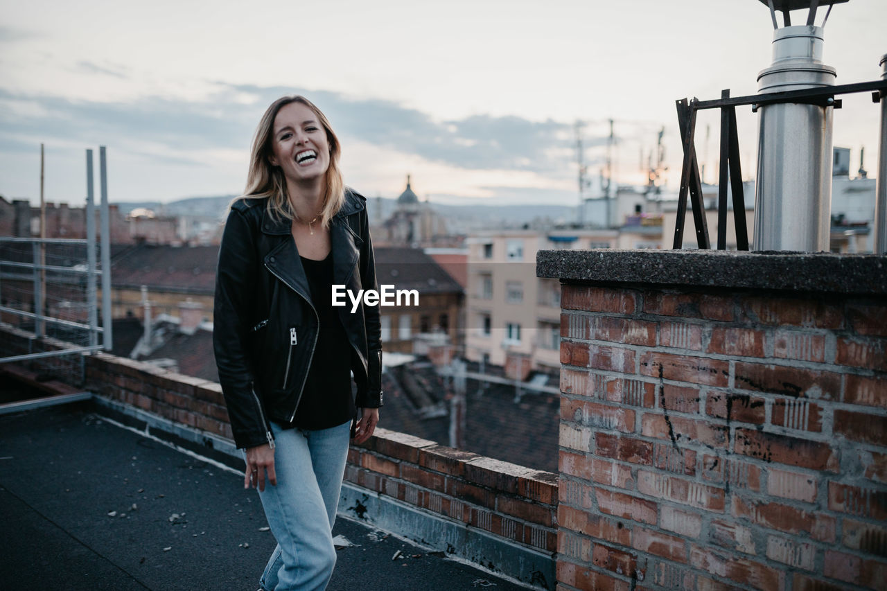 Portrait Of Smiling Young Woman Standing Against Cityscape During Sunset