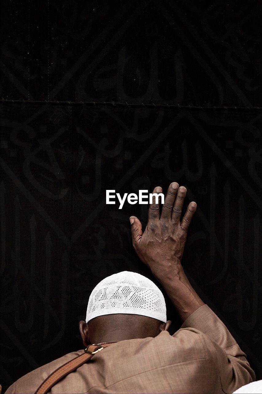 Rear View Of Muslim Man Touching Kaaba While Praying At Al-Haram Mosque