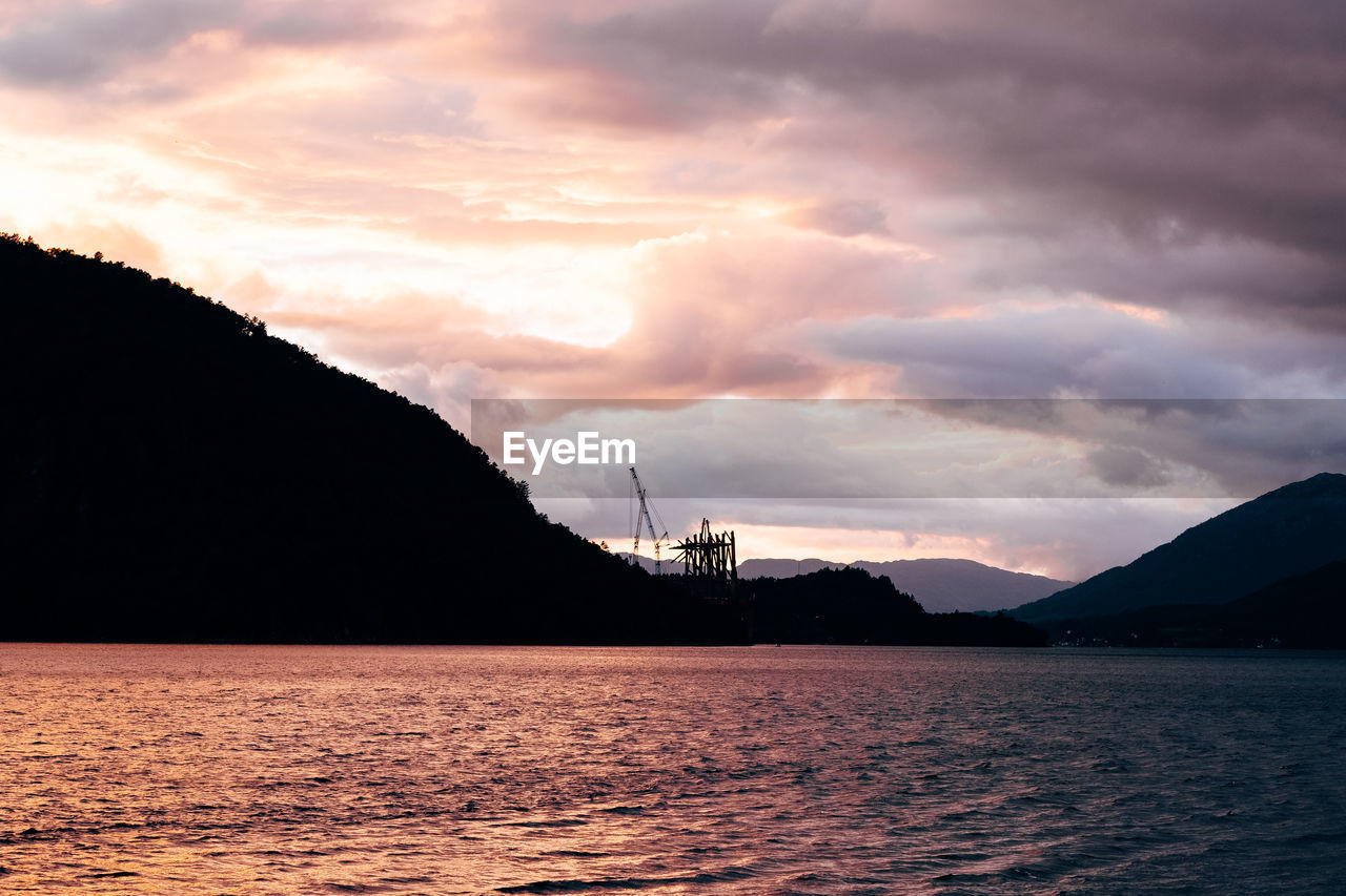 Silhouette Mountain By Sea Against Sky During Sunset