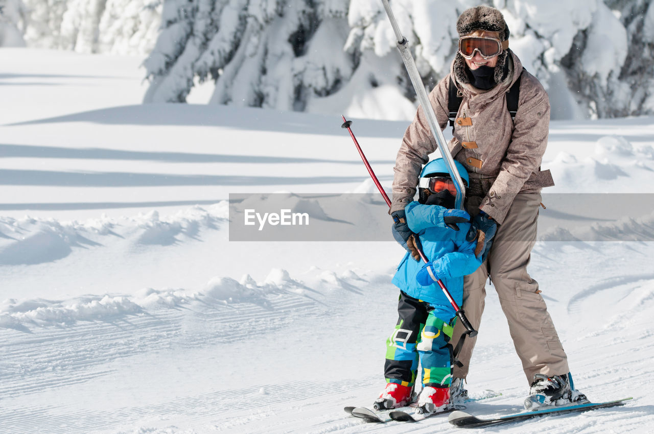 Portrait Of Mature Woman Teaching Son Skiing On Snow Covered Field