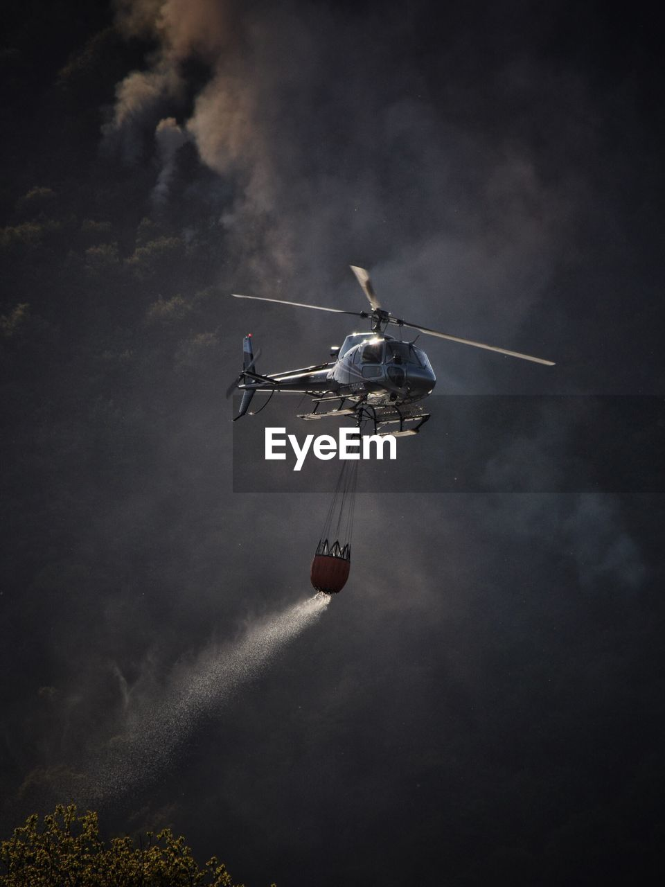 Low Angle View Of Helicopter Flying In Sky Fighting Forest Fire