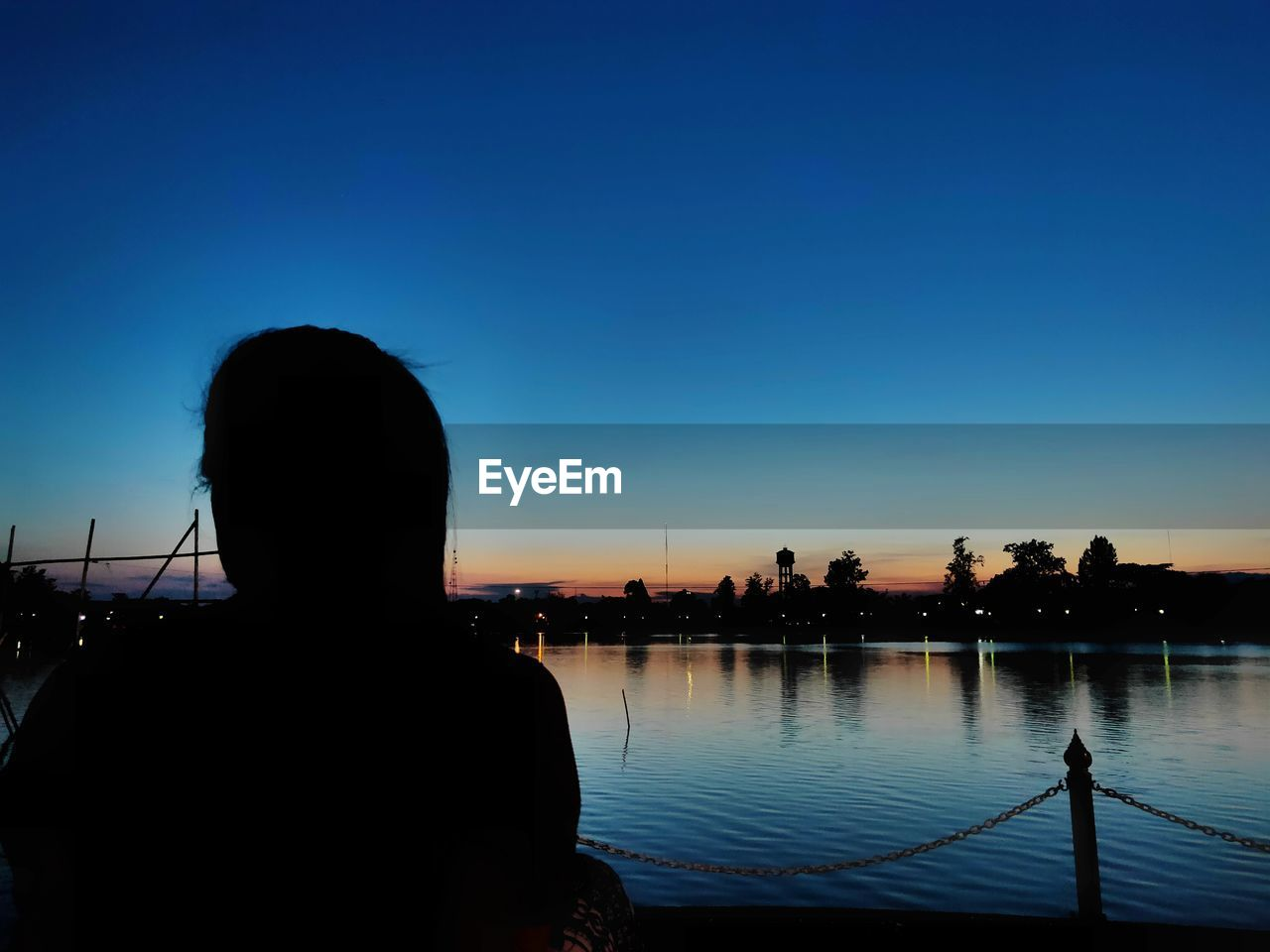 sky, silhouette, real people, one person, lifestyles, leisure activity, rear view, water, clear sky, men, nature, sunset, headshot, portrait, blue, copy space, architecture, built structure, outdoors, looking at view