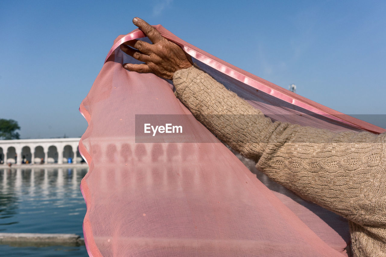 Close-up of woman holding pink veil against clear blue sky