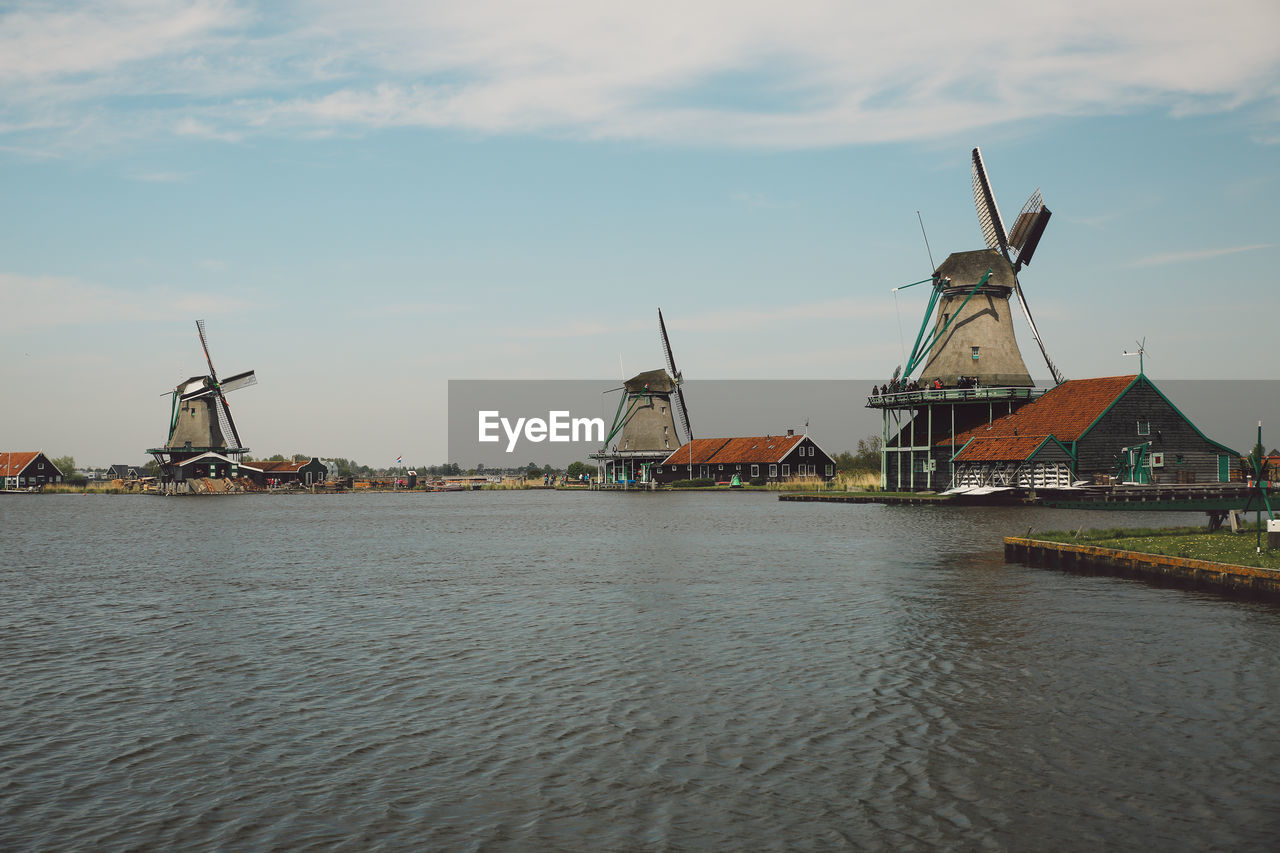 wind power, alternative energy, wind turbine, windmill, renewable energy, environmental conservation, fuel and power generation, traditional windmill, waterfront, sky, industrial windmill, water, cloud - sky, no people, outdoors, day, nature, built structure, nautical vessel, architecture, building exterior, beauty in nature